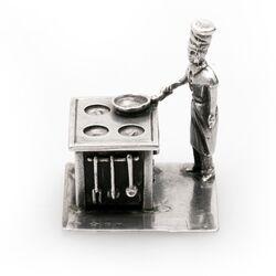 Zilveren miniatuur kok achter zijn fornuis