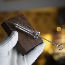 Zilveren injectiespuit op een houten basement