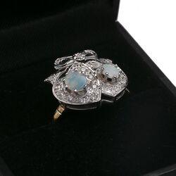 Gouden ring met twee harten bezet met opaal en een strik met diamantjes