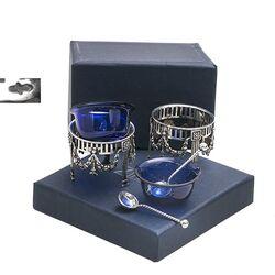 Twee zoutvaatjes met blauw glazen bakjes en zilveren zoutlepeltjes