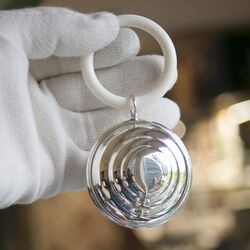 Zilveren rammelaar verhoogd middenstuk parelranden direct graveren